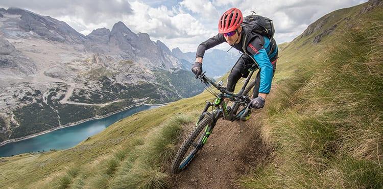 Vår Sportson guide Berner kör hårt på MTB Trails Camp i Dolomiterna, med Marmolada glaciären i bakgrunden.